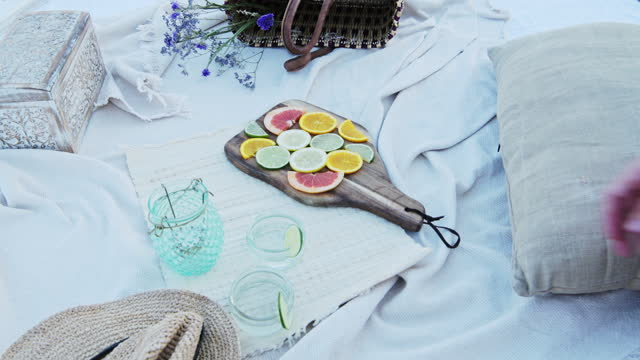 putting freshly sliced citrus fruits on a small wooden chopping board on a picnic blanket - close up - soft focus stock videos & royalty-free footage