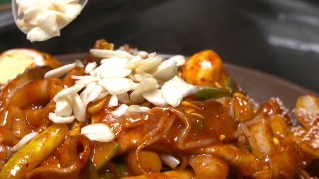 Putting fried garlic on top of Tteokbokki(Stir-fried Rice Cake)