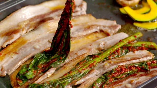 Putting Gat (leaf mustard) Kimchi (Popular traditional side dish in Korea) on top of the grilling pork belly