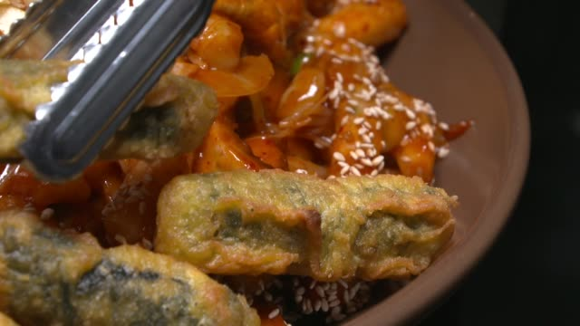 Putting Gim Mari Twigim(Deep-fried Glass Noodles in Seaweed) on top of Tteokbokki(Stir-fried Rice Cake)
