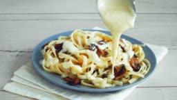 Putting mushroom sauce on tagliatelle spaghetti. Italian pasta.
