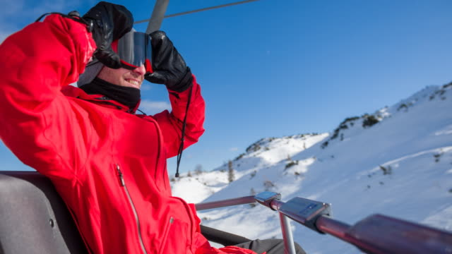 putting on ski goggles while riding on chairlift to top of snowcapped mountain - sitting stock videos & royalty-free footage