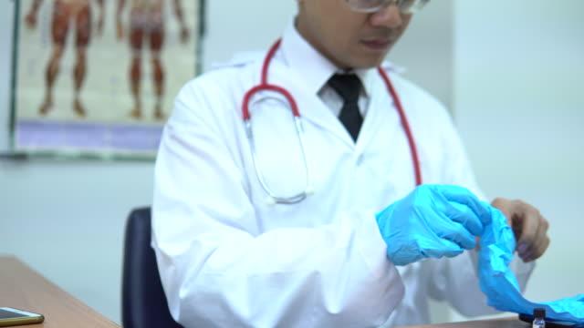 vidéos et rushes de enfilez des gants de chirurgie - vêtements professionnels hospitaliers