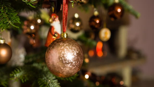 Putting ornament on a christmas tree