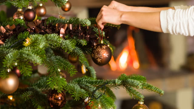 putting ornaments on christmas tree, fireplace burning in background - spruce stock videos & royalty-free footage