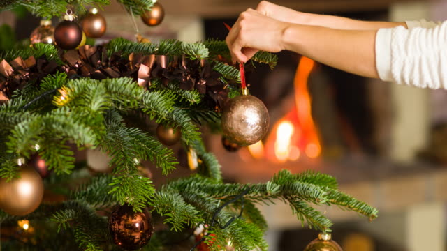 putting ornaments on christmas tree, fireplace burning in background - decoration stock videos & royalty-free footage
