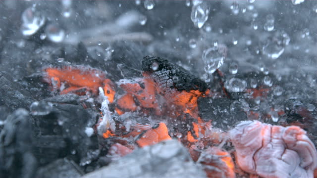 vídeos de stock e filmes b-roll de putting out a fire macro shot of burning coals with water drops and smoke extinguishing flame in slow motion at 1000 fps - flame