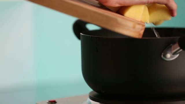 putting potatoes in boiling water - マッシュポテト点の映像素材/bロール