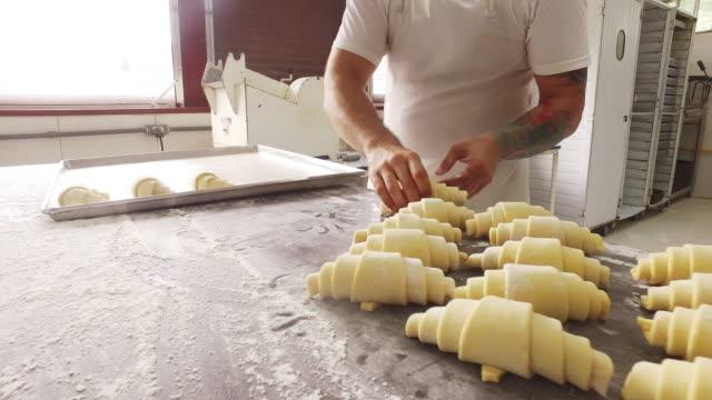 stockvideo's en b-roll-footage met het zetten van opgerolde croissants op een bakplaat - bakkerij