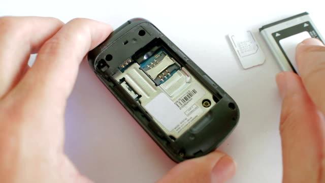 vidéos et rushes de putting-carte sim de téléphone mobile - batterie