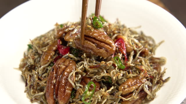 putting stir-fried anchovies with pecan in a plate / south korea - anchovy stock videos & royalty-free footage