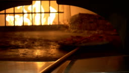 Putting the pizza in the burning oven