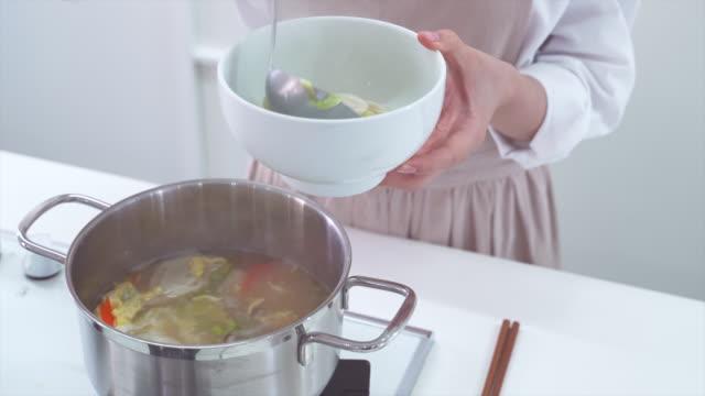 putting tteok mandu guk (korean rice cake soup with dumplings) into a bowl - korean new year stock videos & royalty-free footage