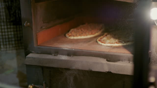 putting two pizzas in hot oven - kitchen utensil stock videos & royalty-free footage