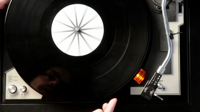 stockvideo's en b-roll-footage met putting vinyl disc on turntable - draaitafel