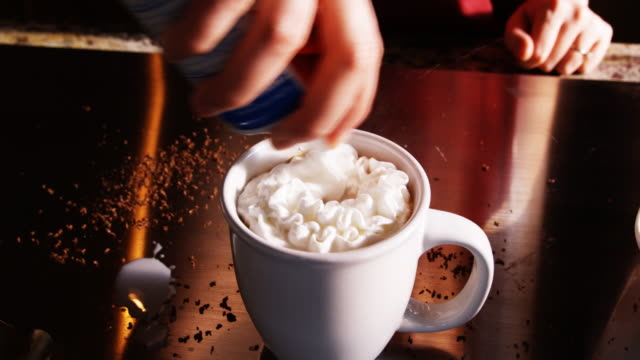 putting whipped cream on a mug of hot chocolate - hot chocolate stock videos and b-roll footage