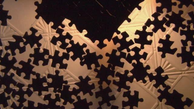 vídeos de stock, filmes e b-roll de la cu puzzle pieces on glass table/ zo ms puzzle pieces as ceiling fan spins above them/ brooklyn, ny - ventilador de teto