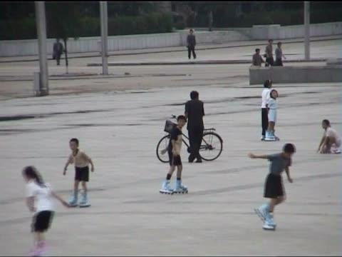 pyongyang: ext gv children roller-blading in kim il sung square man skating along communist flag flying above square where people are roller blading... - communist flag stock videos & royalty-free footage