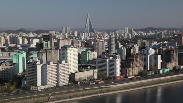 pyongyang's modern skyline stretches along the taedong river. - pyongyang stock videos and b-roll footage