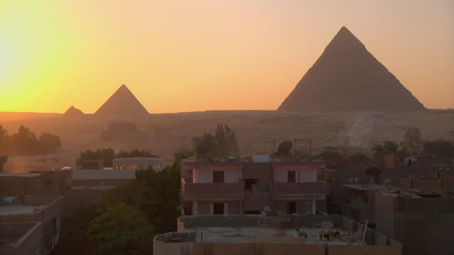 vídeos de stock, filmes e b-roll de ws pyramids against sunset  with rooftops and houses in foreground / giza, egypt - cultura egípcia