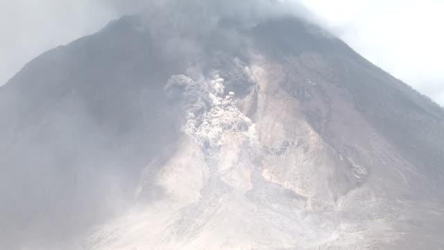 vídeos y material grabado en eventos de stock de pyroclastic flow and rock fall during volcanic eruption at mount sinabung - monte sinabung