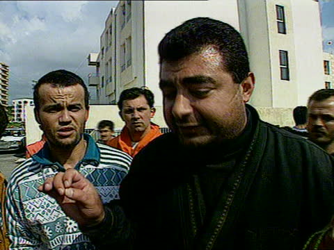 israel shells un base; lebanon: tyre: najin hospital: ext female medical worker helping injured man up steps to hospital l, tilt up men run twds... - female doctor stock videos & royalty-free footage