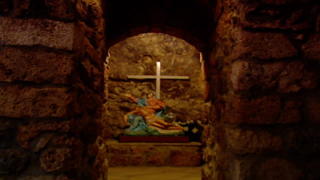 qannoubine valley, mount lebanon. long shot of a crucifix and a statue that depicts virgin mary and jesus inside mar licha monastery. - old stock videos & royalty-free footage