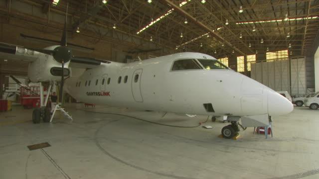 qantas dash 8 (bombardier) in hangar, australia - hangar stock-videos und b-roll-filmmaterial