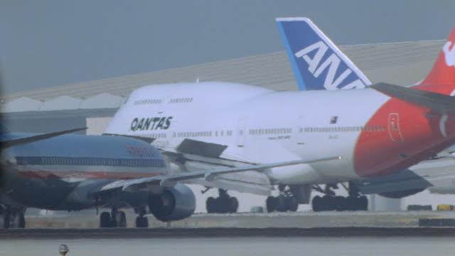 stockvideo's en b-roll-footage met a qantas jumbo jet taxis on the tarmac at los angeles international airport. - smog