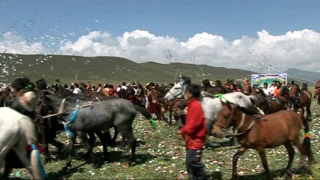 tibetans along with horses as paper rains down - plateau stock videos and b-roll footage