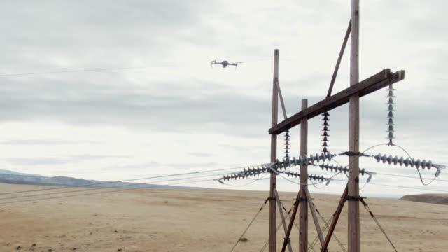 vídeos de stock, filmes e b-roll de um zangão do quadcopter inspeciona linhas eléctricas no vale grande de colorado ocidental um céu em parte nebuloso - torre estrutura construída