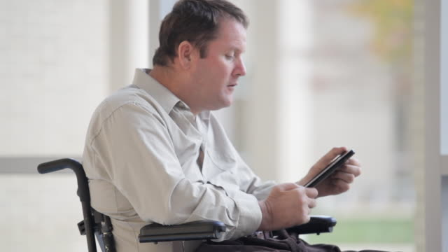 a quadriplegic man struggles with a tablet in his hands. - paralysis stock videos & royalty-free footage