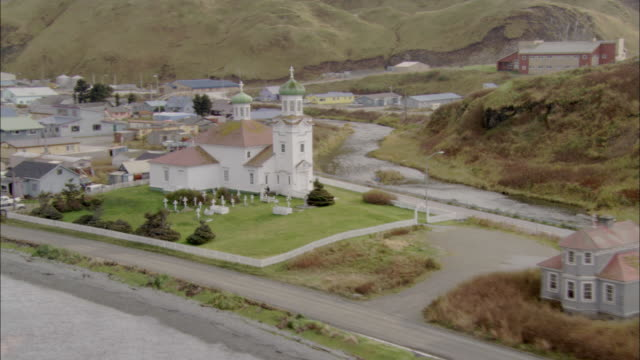 a quaint church with spires and a cemetery border the alaskan coast along with other buildings and houses. - spire stock videos & royalty-free footage