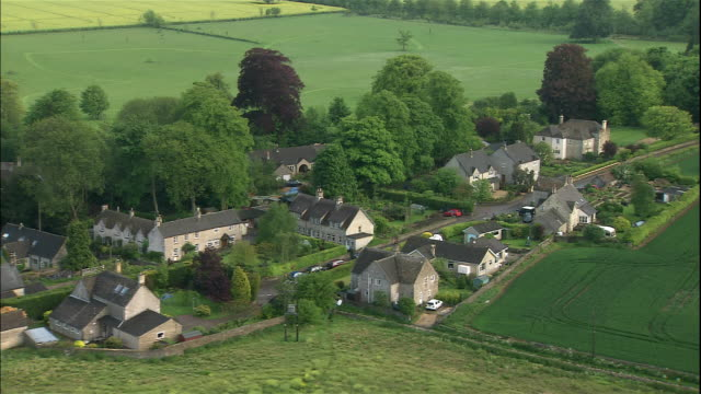 quaint houses line the road and green fields in a small village in cotswolds, england. - cotswolds stock videos & royalty-free footage