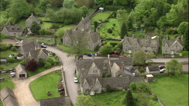 quaint houses line the road in a small village in cotswolds, england. - cotswolds stock videos & royalty-free footage