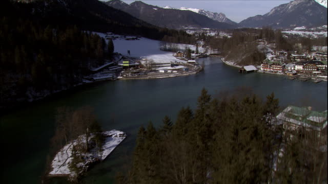 stockvideo's en b-roll-footage met a quaint village lies on the snowy banks of lake konigssee with the bavarian alps in the background in bavaria, germany. - bavarian alps