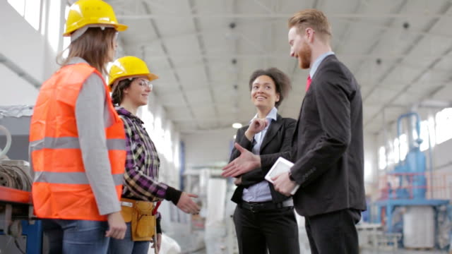 Quality inspector shaking hands with factory worker