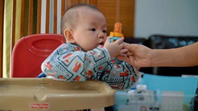 karantän: pojke äter frukt hemma - 6 11 månader bildbanksvideor och videomaterial från bakom kulisserna