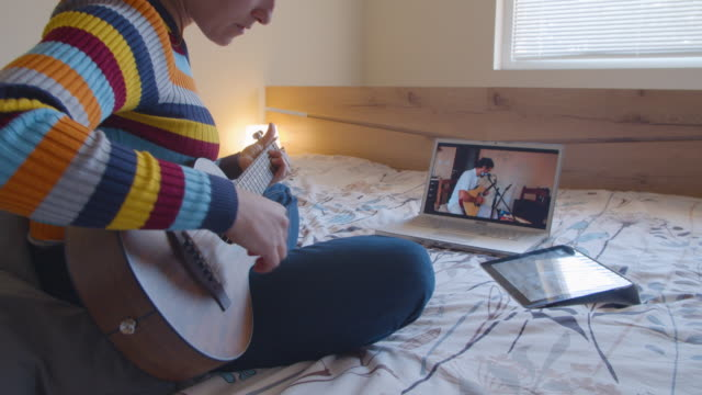 vídeos de stock e filmes b-roll de covid-19 quarantine. friends playing music together through a video call on the internet. music band repetition online. having fun while staying at home. - eco