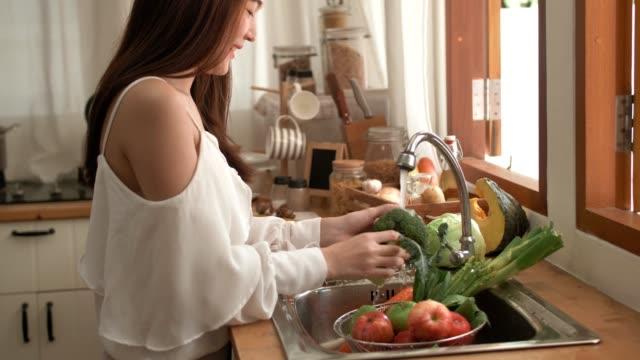 quarantine : woman washing vegetables at home - freshness stock videos & royalty-free footage
