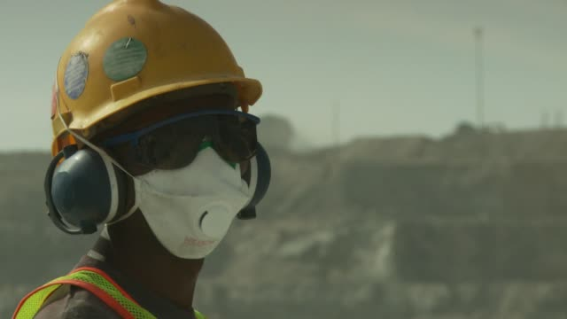 a quarry employee wears protective gear as he works. available in hd. - miniera video stock e b–roll