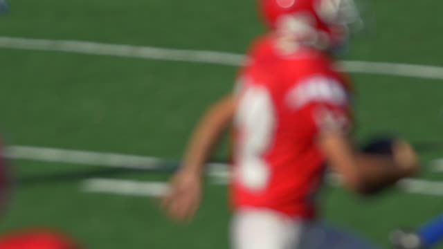 a quarterback and men playing american football. - kopfbedeckung stock-videos und b-roll-filmmaterial