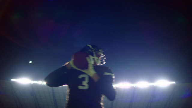 vídeos de stock, filmes e b-roll de ms la slo mo quarterback dropping back and throwing pass during football game at night - bola