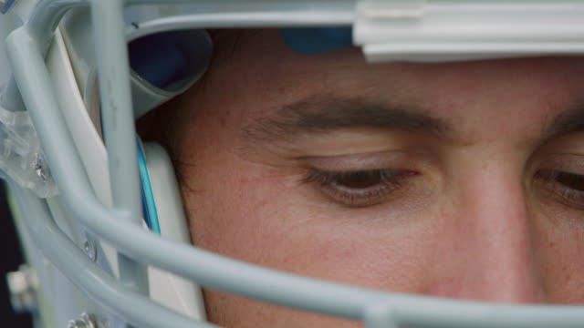 ECU SLO MO. Quarterback in football helmet scans playing field with eyes and stares into camera.