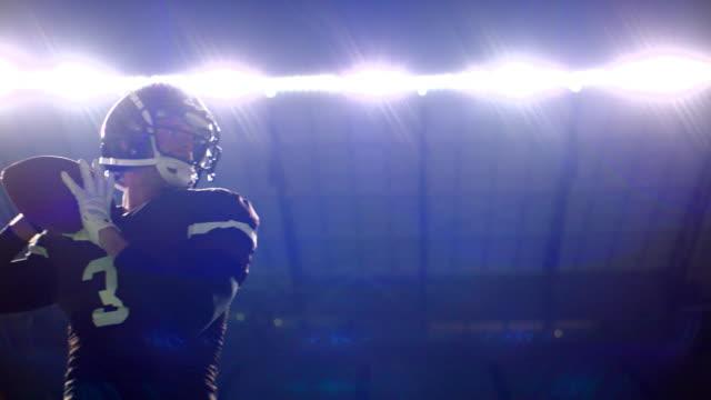 MS LA SLO MO Quarterback throwing football in stadium at night during game