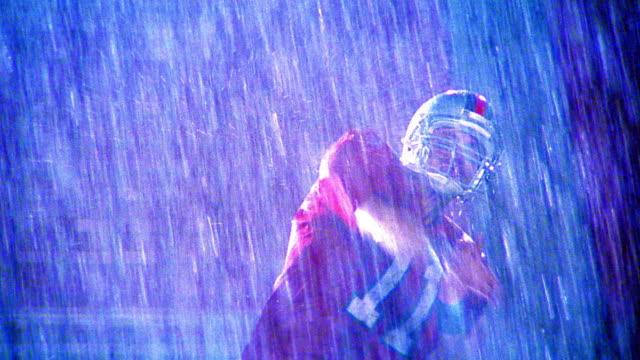 MS quarterback throwing football then raising fist in celebration / rain