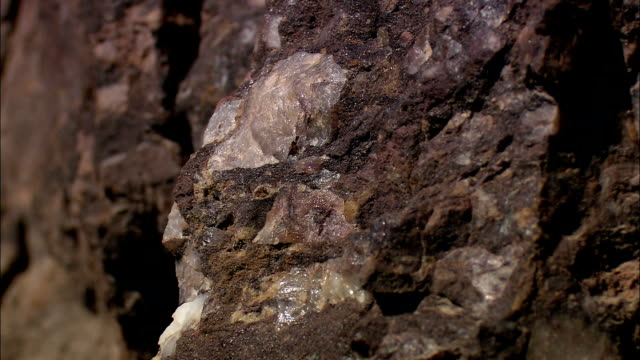 quartz deposits and other silicates shine on the surface of a rock wall. - quarzo video stock e b–roll