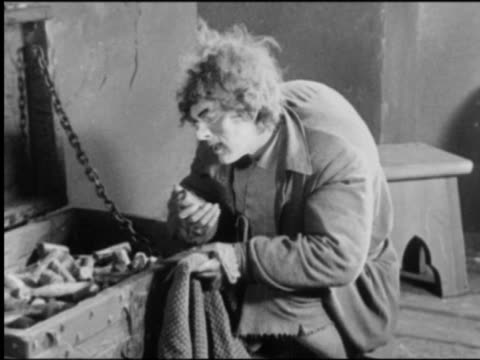 b/w quasimodo (lon chaney) taking objects from trunk holding against chest then putting them in bag - circa 15th century stock videos & royalty-free footage