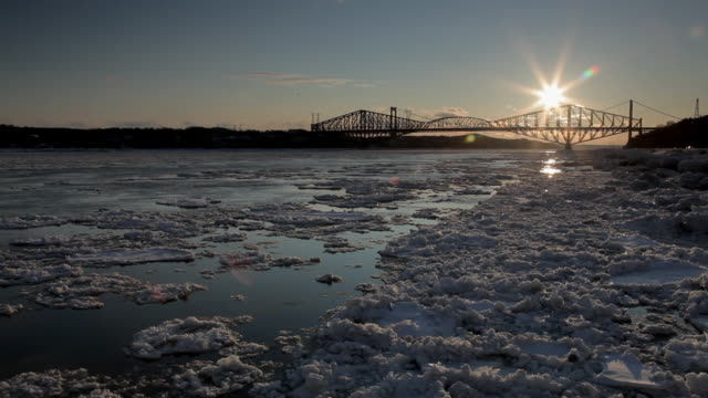Quebec City's bridge with sun over and iced cold water under