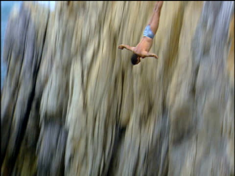 quebrada cliff diver leaps from rock face into sea mexico - cliff stock videos & royalty-free footage